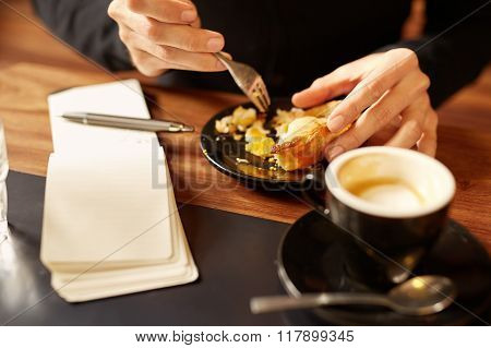 Hands of person enjoying a pastry in modern coffee shop