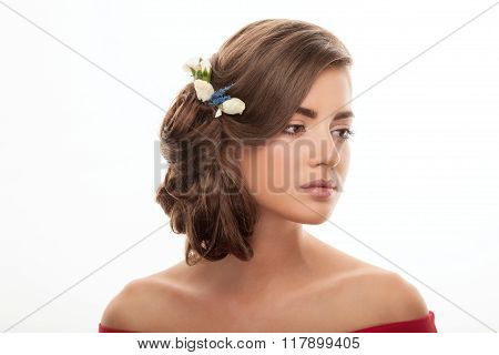 Closeup portrait of young adorable brunette woman with flower headpiece and cute makeup posing on wh
