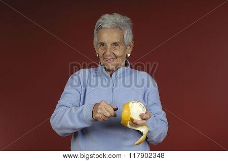 Senior Woman Peeling an Orange