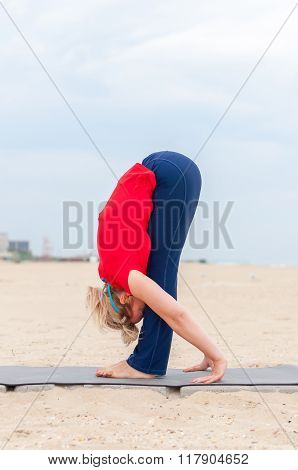 Sporty girl doing Supported Headstand, yoga asana Uttanasana on coast background