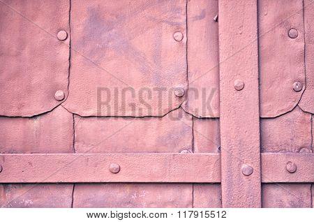 Grunge Surface Of Old Metal Dark Pink Door With Rivets. Industrial Textured Background