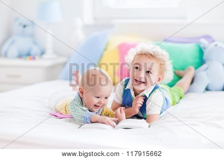 Little Brothers Reading A Book In Bed
