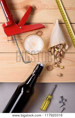 Bottle of beer, pistachio nuts and work tools on wooden planks. Flat lay, top view.