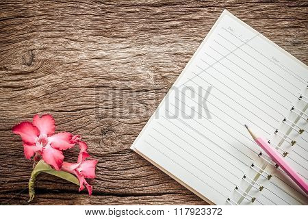 Notebook And Desert Rose Flowers On Old Wooden Background. Vintage Style.