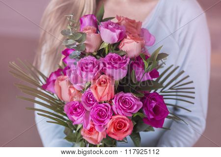 Woman holding a bouquet of beautiful pink roses