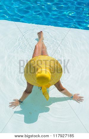 Unrecognizable woman wearing a big hat relaxing at the swimming pool