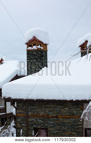 Chimney and chalet roof covered with deep snow
