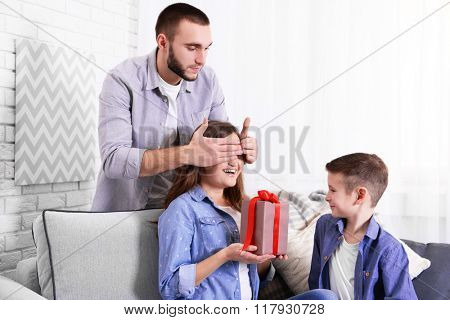 Husband and son giving a gift box to the wife