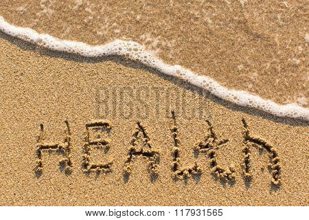 Health - word drawn on the sand beach with the soft wave.
