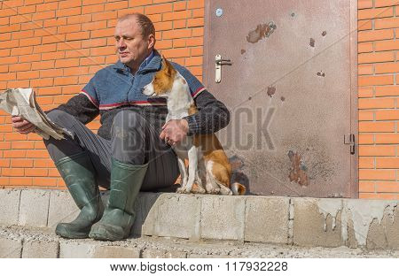 Young dog and mature man reading crumpled newspaper