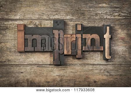 imprint, word written with vintage letterpress printing blocks on rustic wooden background