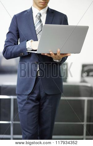 Young businessman with laptop in office