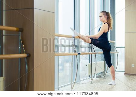 Woman standing near barre in fitness center