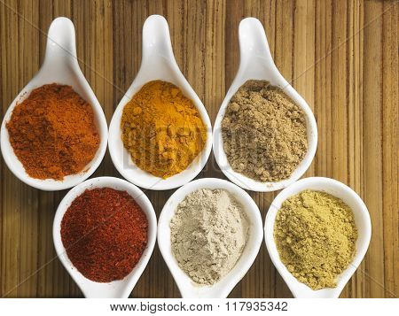 top view of assorted spices powder in saucers