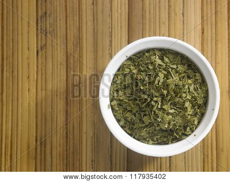 dried parsley in a bowl on the bamboo background