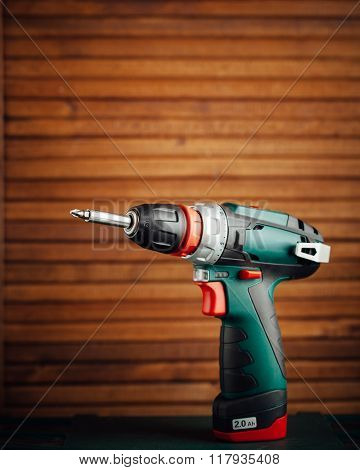 cordless screwdriver against wooden background