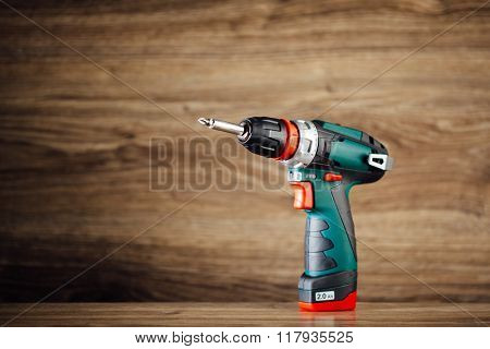 electric screwdriver against wooden background