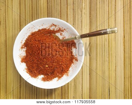 chili powder in a bowl on the bamboo background