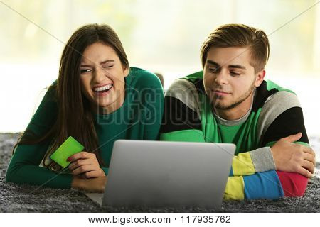 Young happy couple using credit card with laptop at home on light background