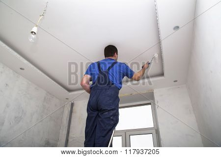 Man worker paints the ceilin inside of the room interior