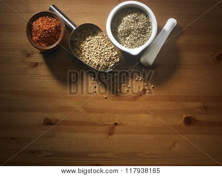 scoop of coriander seeds and cumin in mortar and chili in a bowl