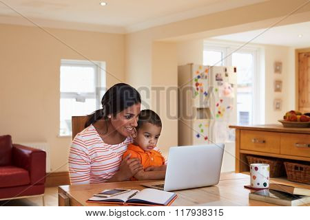 Mother And Son In Kitchen Looking At Laptop Together