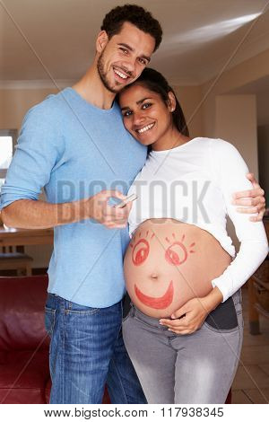 Man Drawing Smiley Face On Pregnant Woman's Stomach