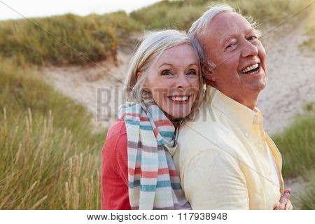 Portrait Of Senior Couple Standing By Sand Dunes