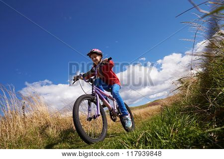 Low Angle Shot Of Girl Riding Bike Through Countryside