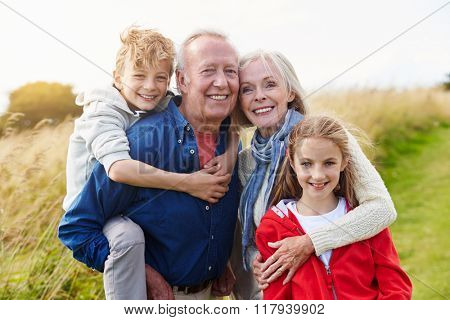 Grandparents With Children On Walk Through Countryside