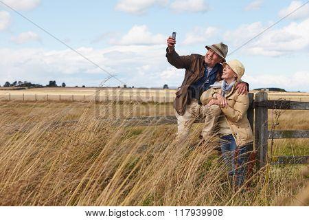 Senior Couple On Walk Taking Selfie On Mobile Phone
