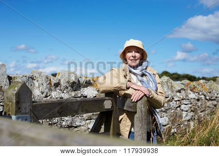 Senior Woman On Walk Leaning Against Wooden Gate