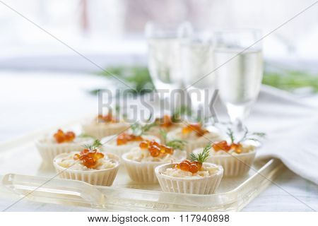 Tartlets with cream cheese and red caviar close up