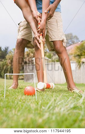 Two people playing croquet