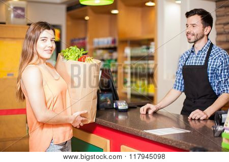 Woman At Checkout Counter In A Grocery Store
