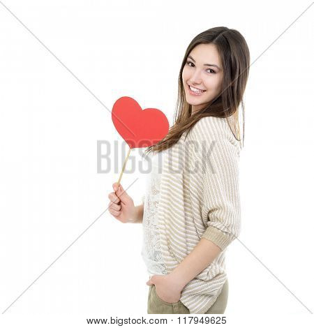 Portrait of attractive happy smiling teen girl with red heart, love holiday valentine symbol over white background