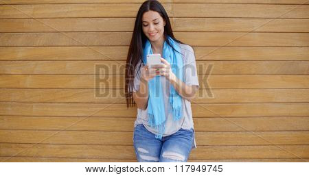 Woman texting while leaning against wall