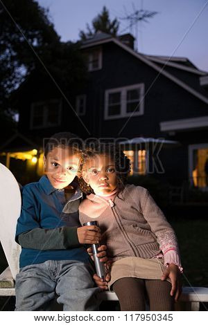Brother and sister with torch on Halloween