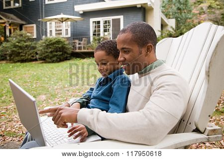 Father and son using laptop in garden