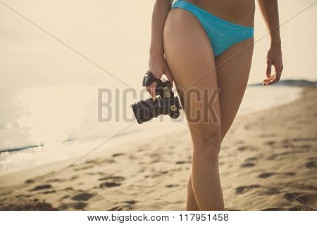 Woman photographer on vacation shooting.Photographer taking pictures with dslr camera on the beach.Professional travel destination photography.Summer memories.Capturing moment of life.Holding camera