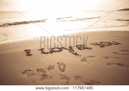 I love you sign written on sunset summer sand beach. Proposal on summer vacation. Romantic engagement. Vintage instagram filter.