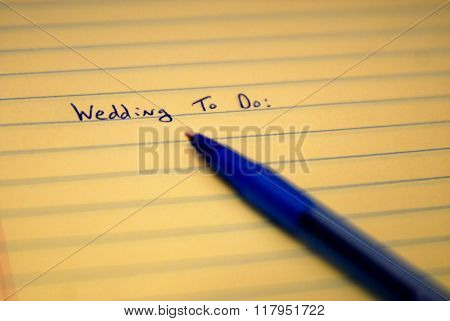 Wedding to do list written on paper with blue pen