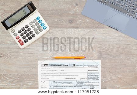 Laptop And Calculator On 2015 Irs Form 1040