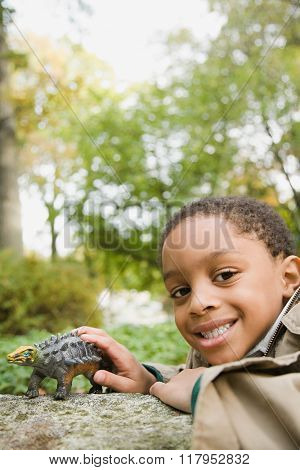 Boy with toy dinosaur