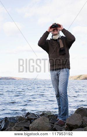 the man using binoculars