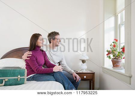 Couple sat on a bed