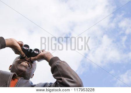 One man looking through binoculars