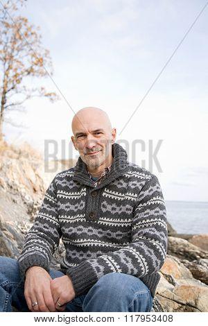 Mature man sitting on rocks