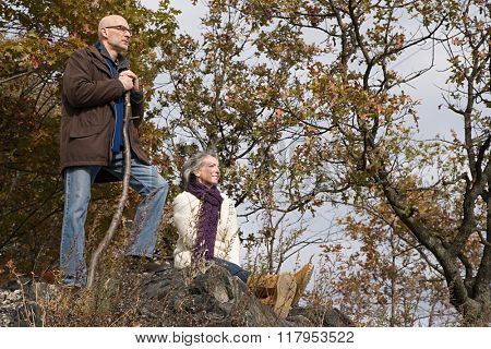 Mature couple resting near trees