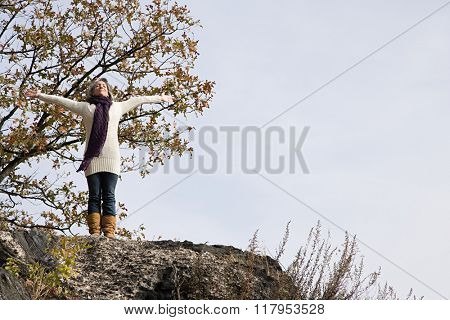 Exhilarated woman standing on rocks